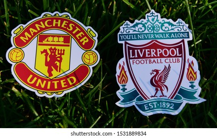 September 6, 2019 London, UK. Emblems of English football clubs Liverpool and Manchester United on the green lawn grass.