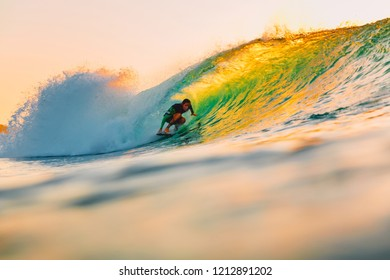 September 8, 2018. Bali, Indonesia. Surfer ride on barrel wave at warm sunset. Professional surfing in ocean, Bingin beach