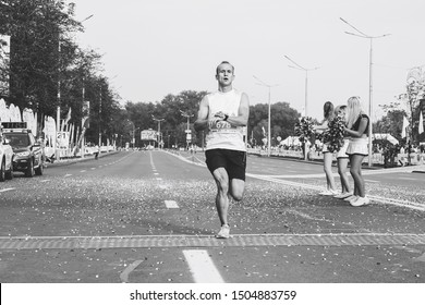September 9, 2018 Minsk Belarus Half Marathon Minsk 2018 Athlete crosses the finish line next to the cheerleaders in black and white