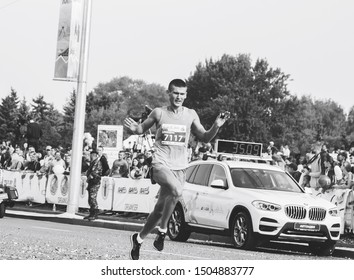 September 9, 2018 Minsk Belarus Half Marathon Minsk 2018 A young athlete runs a marathon next to a special car to accompany participants in the marathon in black and white