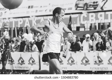 September 9, 2018 Minsk Belarus Half Marathon Minsk 2018 Young athlete runs a marathon next to standing people in black and white