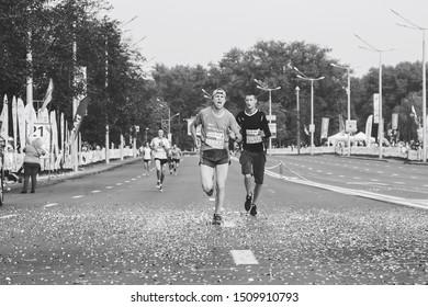 September 9, 2018 Minsk Belarus Half Marathon Minsk 2018 Marathon runner screams overtaking another marathon runner at the finish in black and white