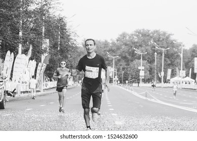 September 9, 2018 Minsk Belarus Half Marathon Minsk 2018 Tired athletes run half marathon on the city road in black and white
