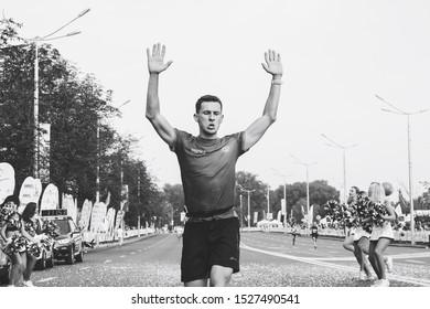September 9, 2018 Minsk Belarus Half Marathon Minsk 2018 Joyful marathon runner screams as he runs along the road strewn with confetti in black and white
