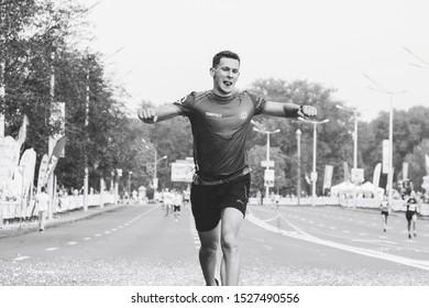 September 9, 2018 Minsk Belarus Half Marathon Minsk 2018 Joyful tired marathon runner ran to the finish line in black and white