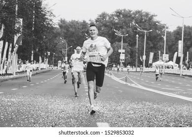 September 9, 2018 Minsk Belarus Half Marathon Minsk 2018 A tired marathon runner runs ahead of other people along the road in black and white