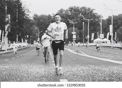 September 9, 2018 Minsk Belarus Half Marathon Minsk 2018 Tired athlete runs ahead of other people on the road in black and white