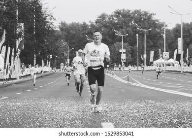 September 9, 2018 Minsk Belarus Half Marathon Minsk 2018 Tired marathon runner runs along the road in black and white