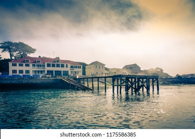 September 9, 2018  Old Coastguard station and buildings in Bandon Oregon photographed from a boat on the Coquille River; fog rolling in