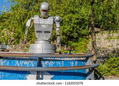 September 9, 2018; Seoul, South Korea: Gray plastic robot sitting on blue metal container at bankrupt amusement park.