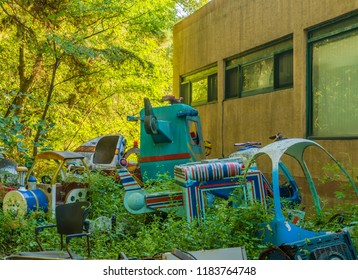 September 9, 2018; Seoul, South Korea: Discarded parts of rides of bankrupt amusement park in disrepair laying on ground in rural wooded area.