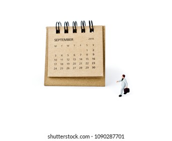 September. Meeting in September. Two thousand eighteen year calendar and miniature plastic businessman on white background. Datebook and travel concept.