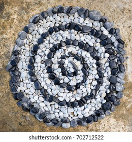 Sequence of black and white stones laid out in the form of a spiral