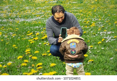 Sequim, Washington- April 1, 2018: A father takes a cell photo picture of his toddler son in a field of dandelions and grass. Cell phones have revolutionized parents' picture taking opportunities.