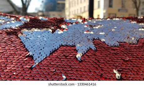 Sequin surface texture with blurred cityscape on background. Silver red two-sided sequins look like contours of continents. Shiny glitter background. Brilliant backdrop. Scales of round sequins