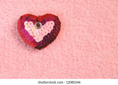 Sequined heart shape on pink soft background