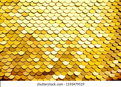 Sequins close-up macro. Abstract background with gold sequins color on the fabric. Texture scales of round sequins with color transition.