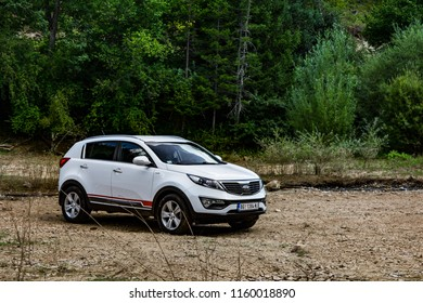 Serbia - 08.01.2018 / car Kia Sportage 2.0 CRDI awd or 4x4, white color, parked in a dried coast of a small lake near lake Zaovine on Mount Tara. With a beautiful mountain landscape in the background