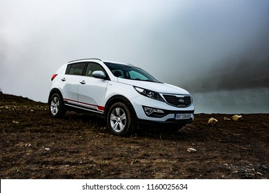 Serbia - 08.01.2018 / car Kia Sportage 2.0 CRDI awd or 4x4, white color, parked in a mudy coast of a lake Zaovine on Mount Tara. With a beautiful forest, and water vapor in the background
