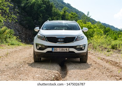 Serbia - 09.21.2018 / car Kia Sportage 2.0 CRDI awd or 4x4, white color, parked on the steep gravel road, near a crack in ground, made by water that drains from the top of a mountain.