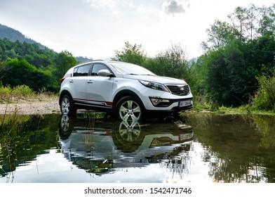 Serbia - 09.21.2018 / car Kia Sportage 2.0 CRDI awd or 4x4, white color,  crossing a lake Lazici, on mountain Tara, near a big cliff, and beautifull countryside, in deep mud wheel spin, great off road