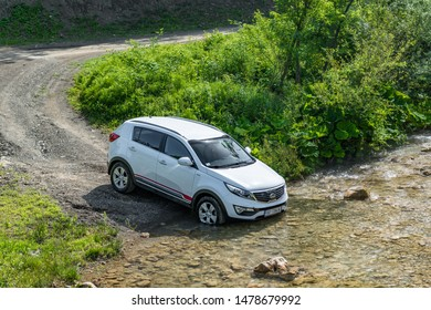 Serbia - 09.21.2018 / Kia Sportage 2.0 CRDI awd or 4x4, white color, crosses the stream ( creeks ), with a very steep approach, and slippery rocks below. SUV car in water