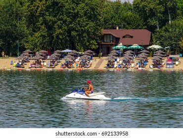 Serbia, Belgrade, Ada Ciganlija lake resort, August 2017. Picture is showing life-guard riding Jet-ski on the lake and a restaurant in the background .