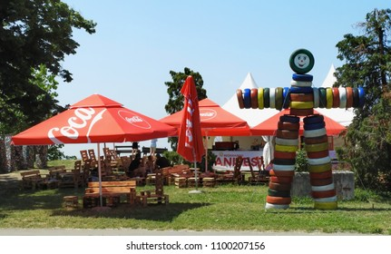 """SERBIA, BELGRADE - May 27th 2018 - Touristic fair called """" Belgrade Manifest """" held on old fortress Kalemegdan, Coca Cola promotional stand with a figure made of colored tires in front"""