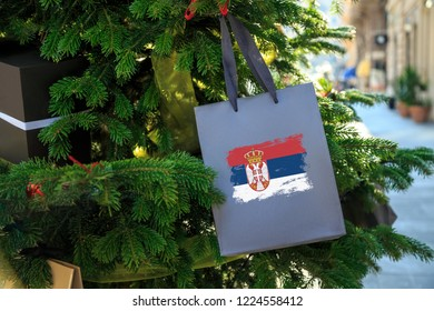 Serbia flag printed on a Christmas shopping bag. Close up of a gift bag as a decoration on a Xmas tree on a street. New Year or Christmas shopping, local market sale and deals concept.
