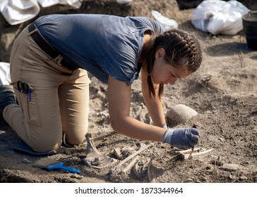 Vinča, Serbia, Sep 27, 2019: Young woman archaeologist working on human remains excavation