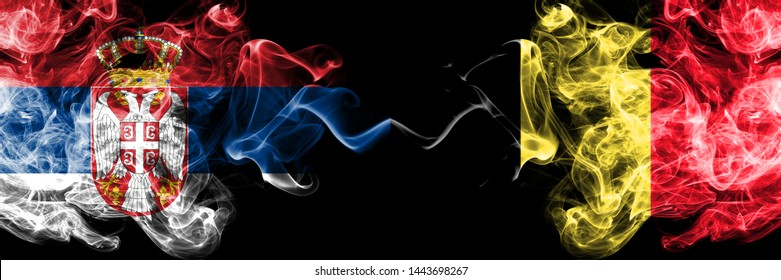 Serbia vs Belgium, Belgian smoky mystic flags placed side by side. Thick colored silky smokes combination of Serbian and Belgium, Belgian flag