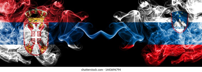 Serbia vs Slovenia, Slovenian smoky mystic flags placed side by side. Thick colored silky smokes combination of Serbian and Slovenia, Slovenian flag