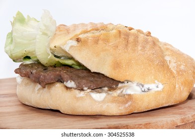 Serbian burger with lettuce served on a wooden board.