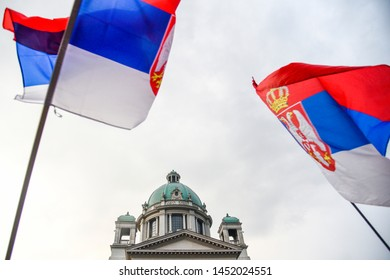Serbian National Assembly and two serbian flags waving