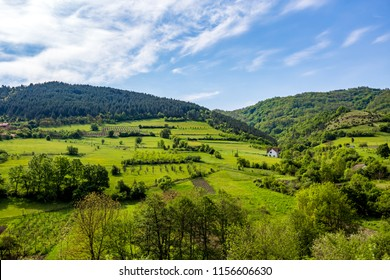 Serbian rural village green springtime landscape, mountains in Serbia are very beautiful, near Valjevo. Valley and hills. White house, farmland and spring forest in spring. European countryside