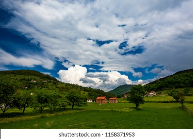 Serbian rural village green springtime landscape, mountains in Serbia are very beautiful, near Valjevo. Valley and hills. White and red houses, farmland and spring forest. Great European countryside