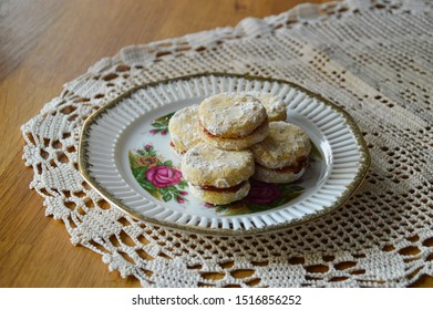 Serbian traditional homemade vanilla cookies (vanilice) on the vintage flower plate and crochet tablecloth