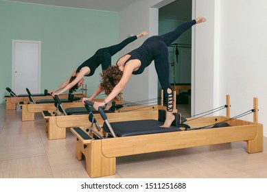 Seregno-Italy 07-17-2019 two women perform pilates exercises in the gym with the help of a bench to keep fit