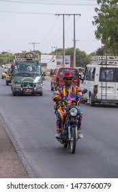 Serekunda, The Gambia - june 23, 2019: Man with multicolored clothes circulating on a motorcycle on the road near the animal market
