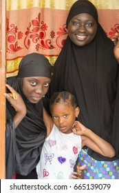 SEREKUNDA, THE GAMBIA - MAY 09, 2017: Young women dressed in Muslim style, at the door of a house, in a neighborhood of the city