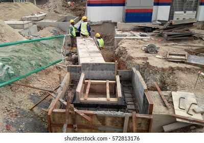 SEREMBAN, MALAYSIA -FEBRUARY 05, 2017: Construction workers installing underground box type precast drain at the construction site.