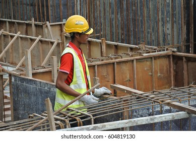 SEREMBAN, MALAYSIA -JANUARY 31, 2017: Construction workers working at the construction site during daytime. They are required to wear proper and suitable safety gear to ensure their safety.