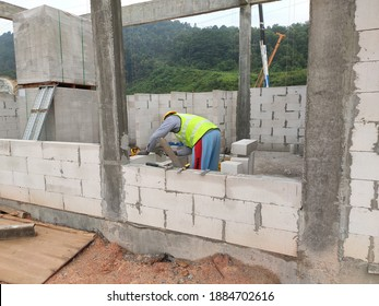 SEREMBAN, MALAYSIA -MARCH 17, 2020: Blockwork by construction workers at the construction site. Workers laying the AAC brick and stacked it together using mortar to form the wall.