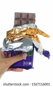 Seremban, Malaysia - November 21, 2019 : A hand hold Cadbury Dairy Milk flavour Hazelnut Bar  cover opened. Picture over a plain white background.