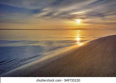 Serene beach and sky, with the sun peeking through playful clouds