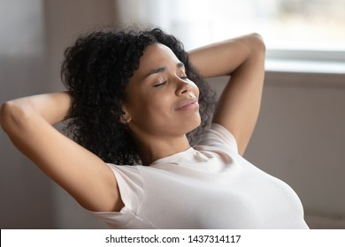 Serene biracial woman putting hands behind head resting indoors, close up millennial female closed eyes daydreaming planning future feeling serenity, no stress reduce anxiety, enjoy of break concept