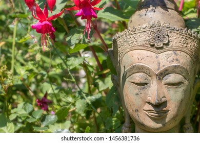 Serene Buddha face garden statue with fuschia flowers. Buddhism at one with nature. Natural world image of traditional Zen Buddhist head with wildflowers and lush green foliage background.