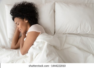 Serene calm african american woman sleeping in comfortable bed lying on soft pillow orthopedic mattress, peaceful young black lady resting covered with blanket on white sheets in bedroom, top view - Shutterstock ID 1444222010