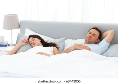 Serene couple sleeping on their bed in the morning at home