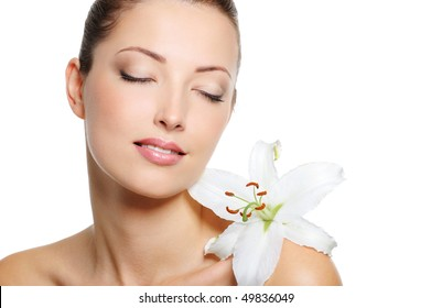 Serene face of a beauty fresh woman with closed eyes and flowe on her shoulder